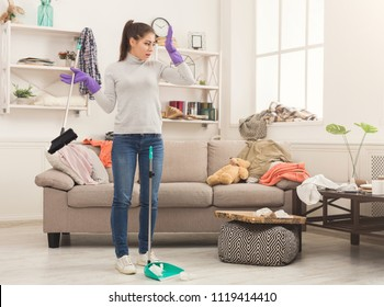 Shocked woman with special equipment cleaning house. Young girl surrounded by many stack of clothes. Disorder and mess at home, copy space
