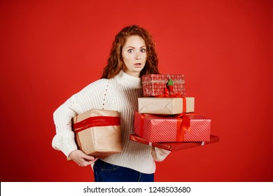 Shocked woman with a stack of christmas presents