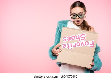 shocked woman in sunglasses looking at box with favorite shoes lettering on pink, black friday concept
