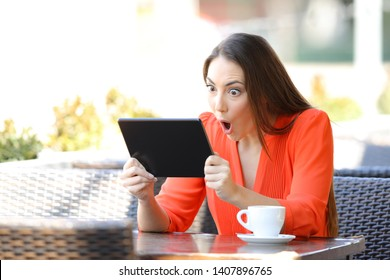 Shocked woman watching and listening media on tablet sitting in a coffee shop terrace