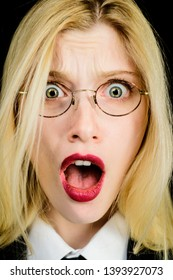 Shocked woman. Woman's portrait. Astonished woman with shocked face and open mouth. Closeup blonde girl in glasses with shocked facial expression. Surprised stunned woman with red lips. Human emotion.