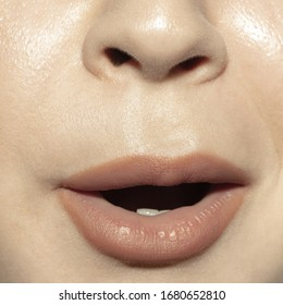 Shocked, wow. Close-up shoot of female mouth with natural nude gloss lips make-up and well kept cheeks skin. Cosmetology, medicine, dentistry and beauty care, emotions and facial expression concept.