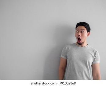Shocked and wow face of Asian man with beard in grey t-shirt.