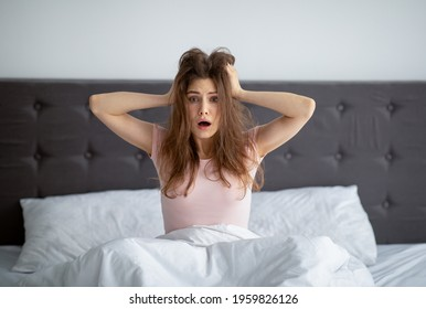 Shocked yound woman sitting in bed at home, grabbing her head in terror, oversleeping, being late to work. Stressed millennial lady having difficulty waking up in mornings