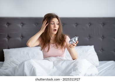 Shocked yound woman staring at alarm clock, sitting on bed at home, grabbing her head in terror, being late for work. Stressed Caucasian lady oversleeping, having trouble waking up in morning