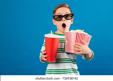 Shocked young boy in eyeglasses preparing to watch the film while holding soda and popcorn over blue background