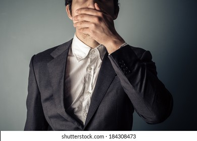 Shocked young businessman covering is mouth