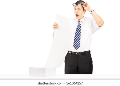 Shocked young businessman reading a document isolated on white background