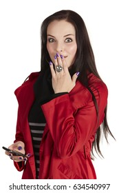 Shocked young caucasian adult woman with long brown hair against a light background, wearing a black dress and red jacket with a mobile phone in her hand