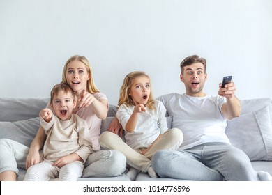 shocked young family watching movie at home and pointing at tv
