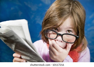 Shocked Young Girl Dressed Up in Reading Glasses Reading a Newspaper