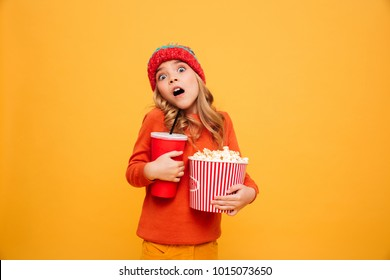 Shocked Young girl in sweater and hat holding popcorn and plastic cup while looking at the camera over orange background
