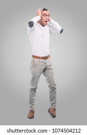 Shocked young man with a gesture of surprise with his mouth openend - Full body shot