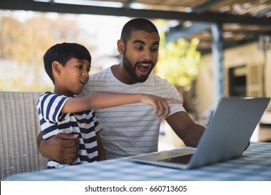 Shocked young man with his son looking at laptop on table