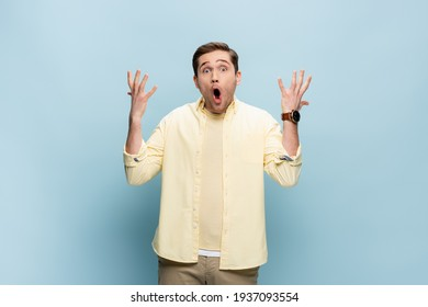 shocked young man looking at camera and gesturing on blue