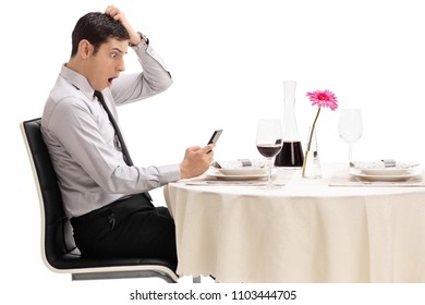Shocked young man looking at his phone seated at a restaurant table isolated on white background