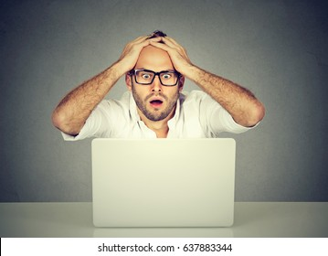 Shocked young man looking at laptop computer anxious with open mouth and big eyes hands on head in disbelief. Human emotion reaction