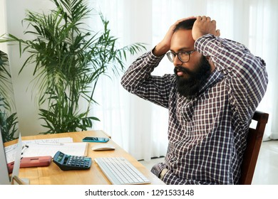Shocked young programmer keeping his hands on head while looking at data on computer screen