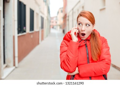 Shocked young redhead woman in red coat surprised talking at mobile phone European city street on background