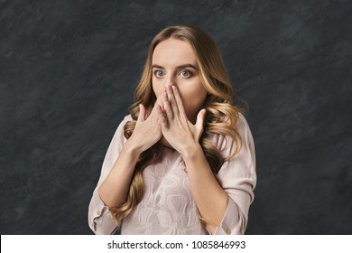 Shocked young woman closing mouth in full disbelief. Surprised girl portrait, gray background. Omg, wtf, human emotions concept