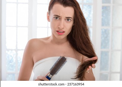 Shocked young woman combing hair with comb in the bathroom. Hair loss