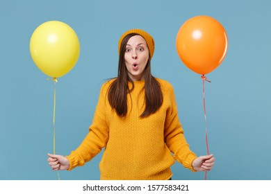 Shocked young woman girl in sweater hat posing isolated on blue background studio portrait. Birthday holiday party, people emotions concept. Mock up copy space. Celebrating hold colorful air balloons