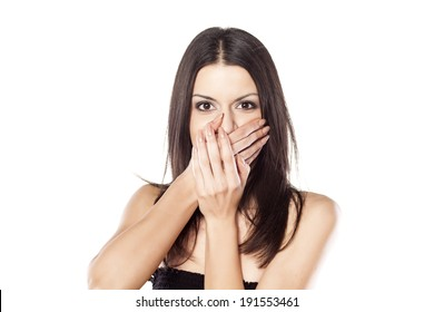shocked young woman with hands over mouth