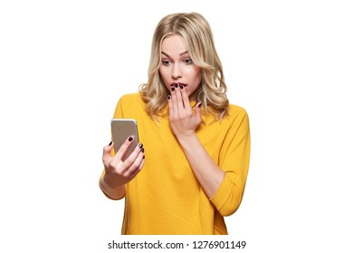 Shocked young woman holding up her mobile phone, reading shocking news. Woman in disbelief, isolated over white background.