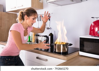 Shocked Young Woman Looking At Cooking Pot With Fire Near Modern Gas In Kitchen