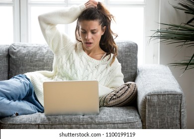 Shocked young woman looking at laptop computer screen at home unpleasantly surprised by email notification message reading bad news online about debt, unexpected rejection, having financial problem