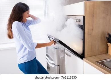 Shocked Young Woman Looking At Smoke Coming From Oven In Kitchen