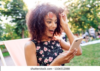 Shocked young woman with open mouth looking on mobile phone . Mixed race girl in trendy dress with surprised face.
