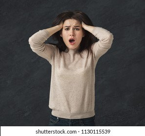 Shocked young woman with opened mouth in full disbelief. Surprised girl portrait, gray background. Omg, wtf, human emotions concept
