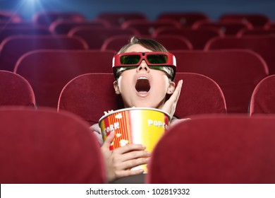 Shocked young woman with popcorn in 3D movie