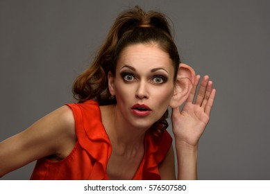 Shocked young woman secretly listening conversation. Hand to ear gesture
