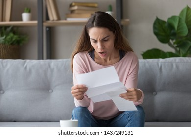 Shocked young woman sit on couch hold paper letter in hands stunned by unexpected unpleasant news, surprised girl reading paperwork document frustrated by bank notice or eviction notification