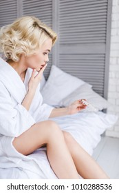shocked young woman sitting on bed and holding pregnancy test