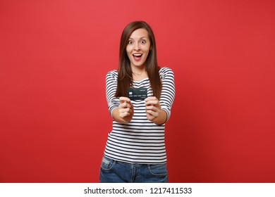 Shocked young woman in striped clothes keeping mouth wide open, looking surprised, holding credit card isolated on red wall background. People sincere emotions, lifestyle concept. Mock up copy space