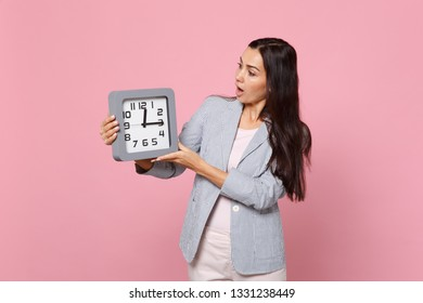 Shocked young woman in striped jacket keeping mouth open holding, looking on square clock isolated on pink pastel background in studio. People sincere emotions, lifestyle concept. Mock up copy space