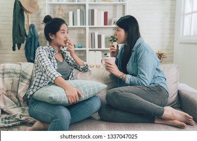 shocked young woman telling her girlfriend some surprised secret. Two asian girls gossiping. Excited emotional female talking chatting to friend while sitting on couch sofa in living room at home.