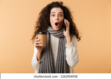 Shocked young woman wearing winter scarf standing isolated over beige background, talking on mobile phone, holding coffee cup