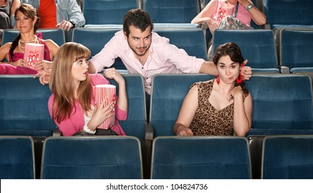 Shocked young women near flirting man in theater