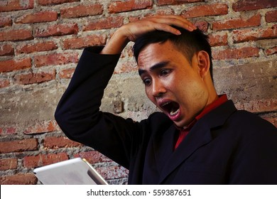 Shocking facial expression by business man after checking work on tablet.