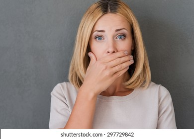 Shocking news. Surprised mature woman covering mouth with hand and staring at camera while standing against grey background