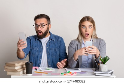 Shocking news at work. Colleagues guy and girl are sitting near, with open mouths and looking at smartphones, in workplace, studio shot