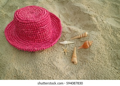 Shocking pink colored straw hat on the sand beach with many types of little seashells, Thailand