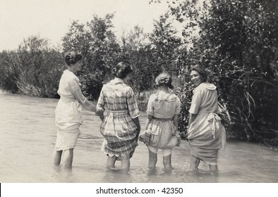 Shockingly High Hemlines - a humorous turn-of-the-century, vintage photograph. Four young women wading in a stream, with their dresses pulled up so high you can see their bare legs and under garments!