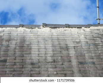 Shoddy roofing work by cowboy builder. Results of rogue worker posing as skilled tradesman. Badly pointed ridge tiles on slate roof, mortar running down tiles. Close up.