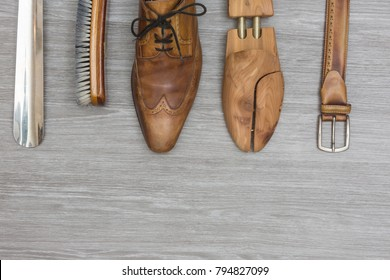 shoe products and a matching belt on a wooden background, topview