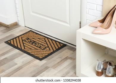 Shoe rack and mat near door in hallway